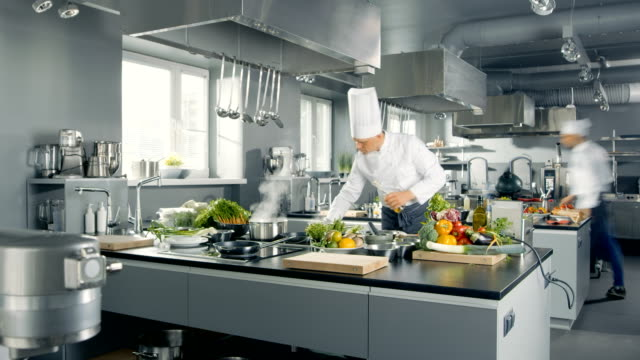 time-lapse panoramic shot of big restaurant kitchen and three chefs working. - chef stock videos and b-roll footage