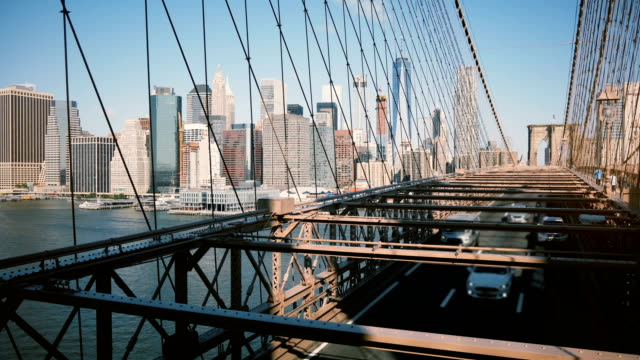 Timelapse panoramic shot of New York seen through Brooklyn Bridge cables. Downtown buildings background on sunny day 4K