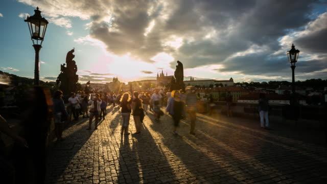 vidéos et rushes de time-lapse 4 k: piétonne bondée pont charles karluv plus tchèque au coucher du soleil - prague