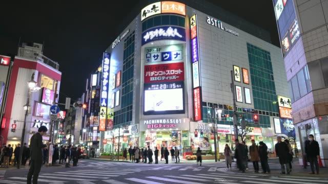 タイムラプス: 新橋地区での歩行者の買い物 (東京・夜) - 街灯点の映像素材/bロール