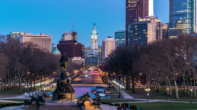 time-lapse: philadelphia city hall along benjamin franklin pkwy from rocky step with city center skylines skyscraper building in downtown pa usa sunset twilight - проспект стоковые видео и кадры b-roll