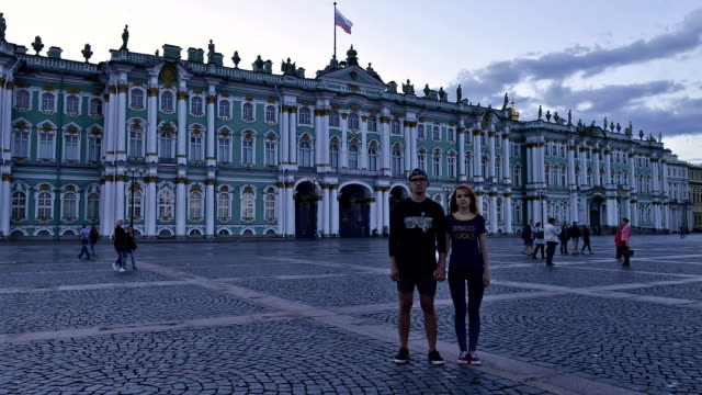 time-lapse photography of a young couple stands on palace square in st. petersburg - san pietroburgo russia video stock e b–roll
