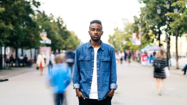 Time-lapse portrait of African American man in casual clothes looking at camera standing in busy street downtown suffering from loneliness when people are passing by.