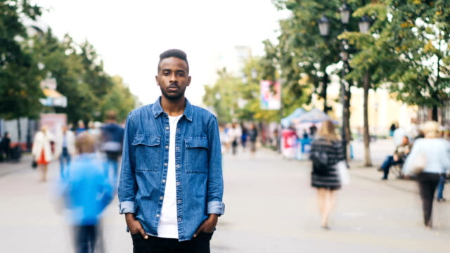 Time-lapse portrait of good-looking African American man lonely person standing in pedestrian street and looking at camera with unhappy face while people are passing by.