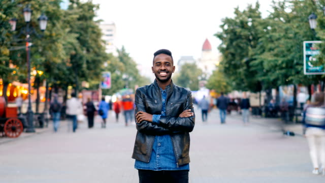 Time-lapse portrait of handsome African American guy standing in the street with arms crossed and smiling looking at camera. Youth, city and time concept.
