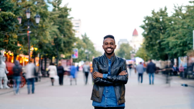 vídeos de stock e filmes b-roll de time-lapse portrait of handsome man african american student looking at camera and smiling standing in the street downlown while people are whizzing around him. - homem casual standing sorrir