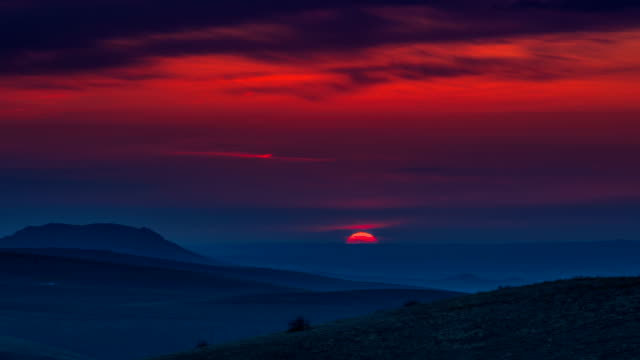 Timelapse Red sunset in the mountains landscape with cloudy sky video