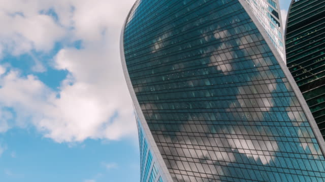 timelapse - reflection of moving white clouds in glass wall of modern skyscraper - contemporary architecture stock videos & royalty-free footage