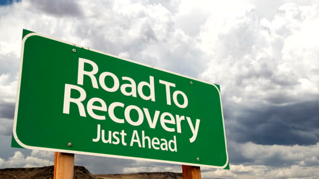 4K Time-lapse Road To Recovery Green Road Sign and Stormy Cumulus Clouds and Rain. video