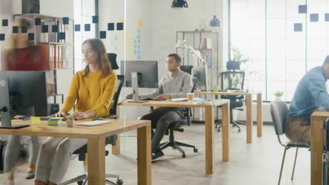 vídeos de stock, filmes e b-roll de time-lapse shot: grupo de funcionários profissionais trabalhando em computadores desktop, andando pelo escritório ocupado. conversando com colegas, projetando software, fazendo suporte ao cliente, enviando clientes - promoção emprego