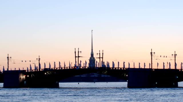 time-lapse skott av öppnandet av palace bridge på kapell av peter och paul fästningen bakgrund tidig morgon - st. petersburg, ryssland - peter and paul cathedral bildbanksvideor och videomaterial från bakom kulisserna