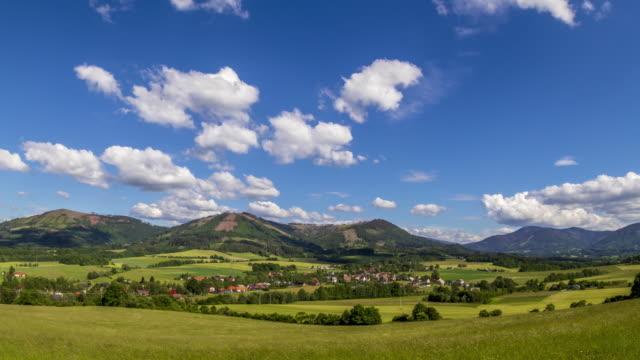 タイムラプスは、村のコズロヴィツェと空に速く動く白い雲の眺めと晴れた日の間にピークの多いベスキーディ山脈の保護地域に位置する山岳風景をスライドします。 - チェコ共和国点の映像素材/bロール