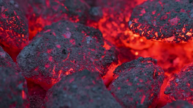 Time-Lapse smoldering coals Time-Lapse shot of сoals smolder and glow. Residual flame from smoldering coals in cinder, closeup view. Flicker of burning coals at night. coal stock videos & royalty-free footage