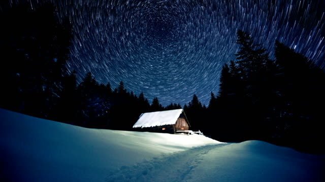 time-lapse. star circles over wooden house in the winter forest - jodła filmów i materiałów b-roll