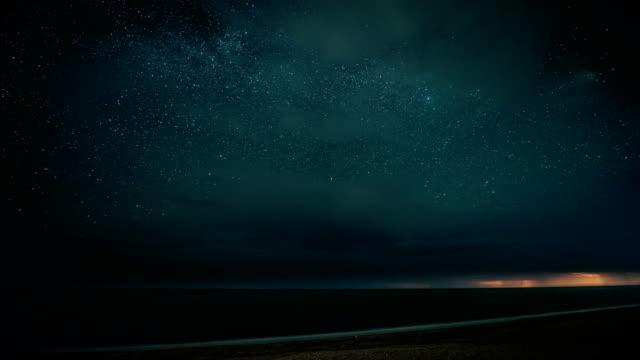 vídeos de stock, filmes e b-roll de lapso de tempo. noite estrelada, com trovões e relâmpagos sobre o mar - horizonte