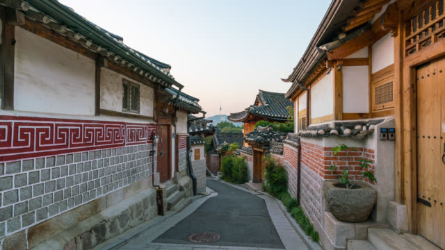 vídeos de stock e filmes b-roll de timelapse sunrise scene of bukchon hanok village at seoul city, south korea. bukchon hanok village is home to hundreds of traditional houses. - seul