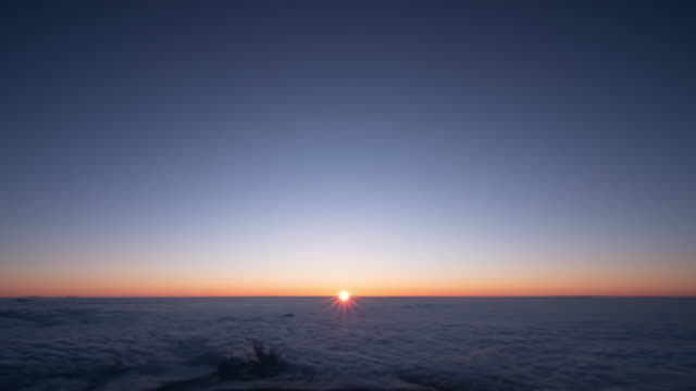 Timelapse - Sunrise viewed from the top of a Fuji mountain Time lapse video taken at the top of Mt. Fuji in Japan. Video of the rising sunrise from the sea of ​​clouds. horizon over land stock videos & royalty-free footage