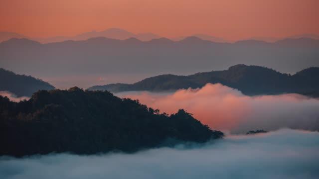 vídeos y material grabado en eventos de stock de lapso de tiempo el mar de niebla está moviendo en la dirección del viento. vista a la montaña por la mañana en tailandia. - norte