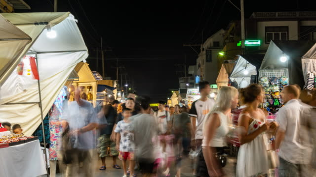 Time-lapse: Tourists visit Hua Hin Night Market. Famous place for both foreign and local visitors. Tilt down