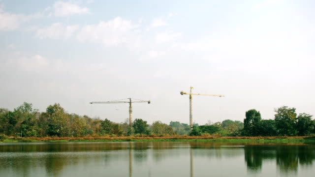 Timelapse Tower cranes are working on construction sites in the forest