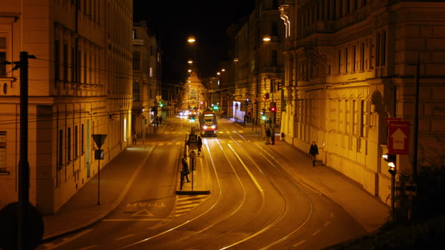 Timelapse tram stop Silingrovo city square in Brno passing through public transport during the night long street
