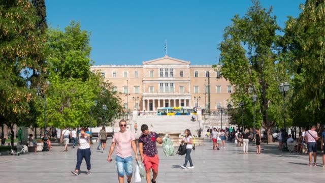 vídeos de stock, filmes e b-roll de lapso de tempo: multidão do viajante no quadrado de syntagma, e edifício do parlamento, definição 4k. - atenas grécia
