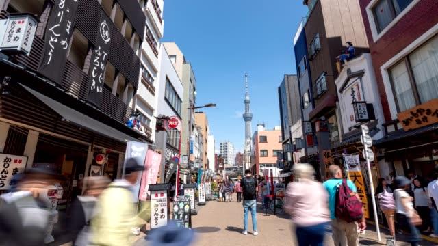 4k time-lapse: traveler fotgängare trångt på marknaden runt asakusa temple, tokyo japan. tilt upp skott - billboard train station bildbanksvideor och videomaterial från bakom kulisserna