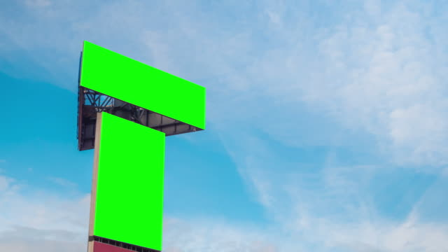 Timelapse - two blank green billboards and moving white clouds against blue sky
