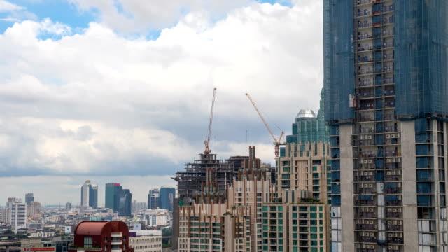 4 k タイムラプス: 建設用クレーンの下で、建物、雨が来る。 - クレーン点の映像素材/bロール