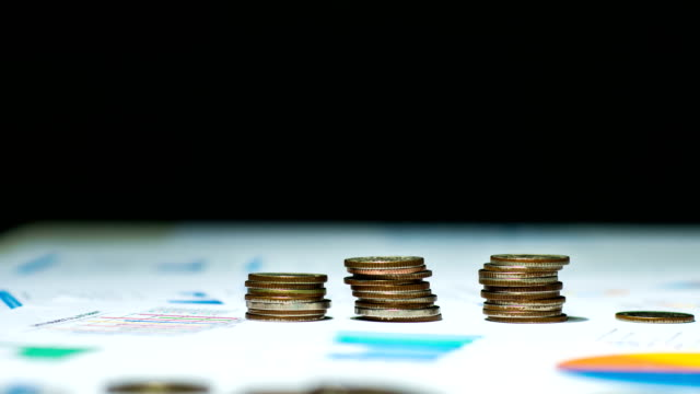Time-lapse video of Stacking Coin on Financial Document, Dolly shot.