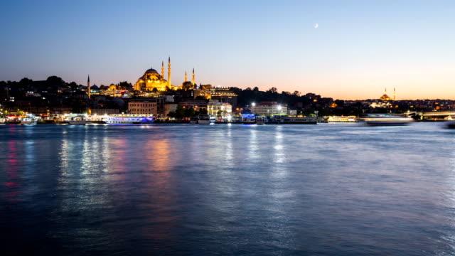 vídeos y material grabado en eventos de stock de vista de timelapse del paisaje urbano de istanbul con mezquita de süleymaniye con barcos turísticos flotando en el bósforo de noche - distrito eminonu