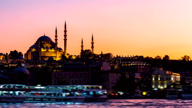 Timelapse view of Istanbul cityscape with Suleymaniye mosque with tourist ships floating at Bosphorus at night video