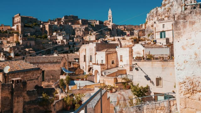 Timelapse view of the Matera old town city in Italy with people rushing through the city.
