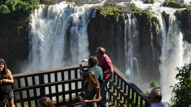 замедленная съемка видом из туристов в игуасу фолс, на границе бразилия и аргентина - парагвай стоковые видео и кадры b-roll