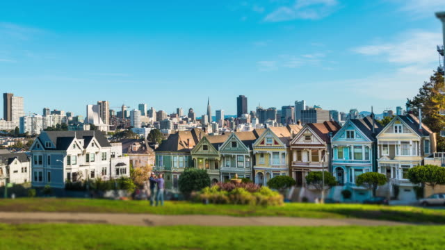 Time-lapse with Victorian homes on Steiner Street with the San Francisco skyline behind. video