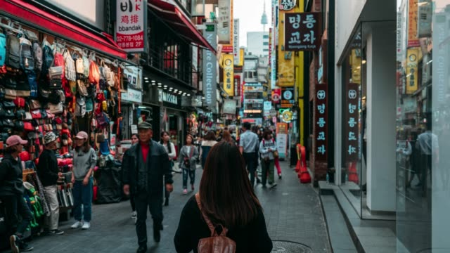 Timelapse Young asian woman traveler traveling and shopping in Myeongdong street market at Seoul, South Korea. Myeong Dong district is the most popular shopping market at Seoul city.