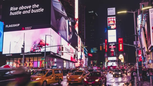 T/L PAN Times Square at night with famous NYC yellow taxis