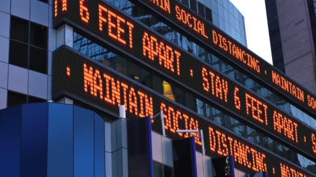 vídeos de stock, filmes e b-roll de ticker times square lembra as pessoas sobre o distanciamento social - new york city