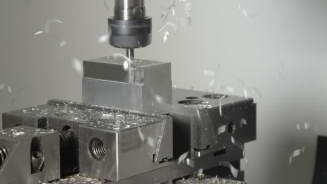 närbild: små chips kommer flygande av en liten metall kub bearbetas av svarv tool - cnc maskin bildbanksvideor och videomaterial från bakom kulisserna