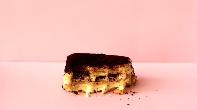 pembe arka planda tirayisu kek. hareket animasyonunu durdur - kek dilimi stok videoları ve detay görüntü çekimi