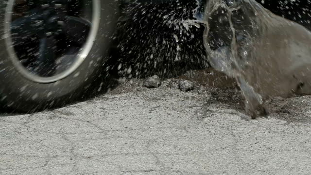 tire hits puddle pothole in slow motion medium shot - кейвинг стоковые видео и кадры b-roll