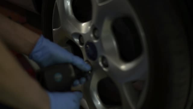 Tire mechanic changing a wheel in mechanical workshop