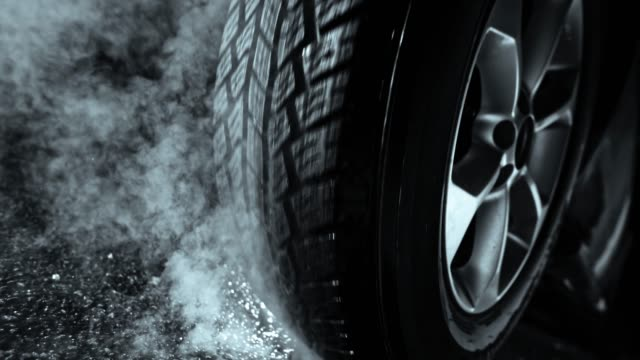 SLO MO Tire rotating on the ground and causing smoke Slow motion wide locked down shot of a car tire being burned against the asphalt causing smoke to emerge. Shot in Slovenia. tires stock videos & royalty-free footage