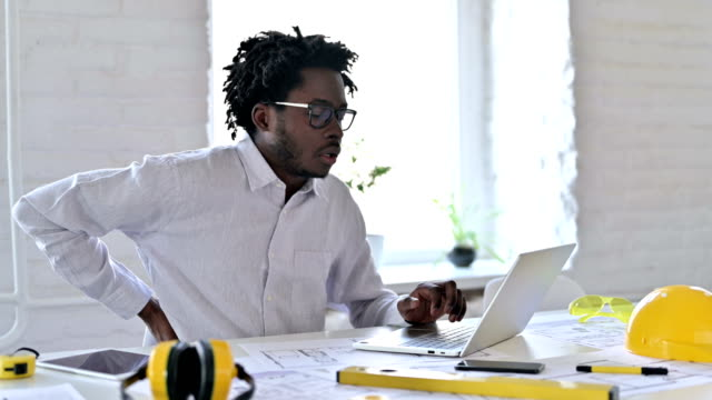 Tired African Architecture Engineer having Back Pain in Office