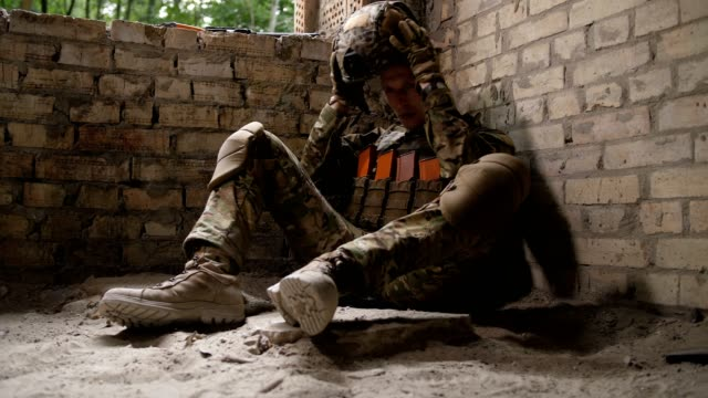 Tired after battle army soldier sitting on ground video