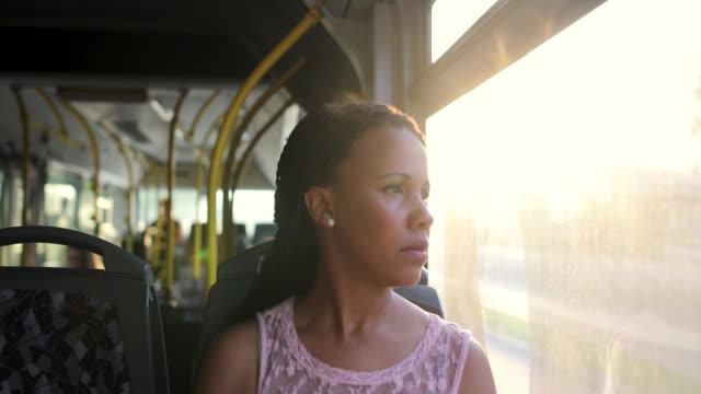 バスに座って窓越しに見ている間、疲れと心配の女性が彼女の問題について考える - 女性 落ち込む点の映像素材/bロール