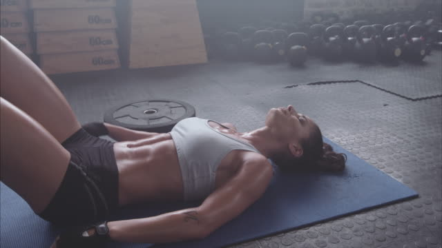 Tired and exhausted female athlete lying on gym floor video