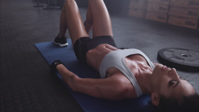 Tired and exhausted sportswoman resting on gym floor Muscular young woman resting on exercise mat at the gym. Female athlete taking a break after intense fitness workout. Tired and exhausted woman taking deep breath. exhaustion stock videos & royalty-free footage
