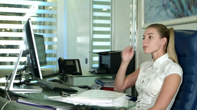 Tired and sleepy young business woman at the desk with a laptop video