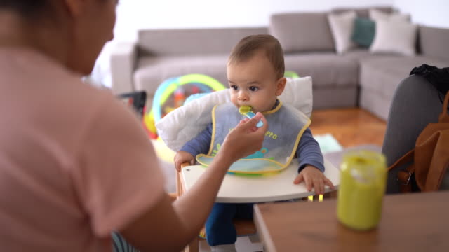 stockvideo's en b-roll-footage met vermoeide baby jongen wrijven zijn ogen terwijl moeder probeert hem te voeden - mid volwassen vrouw